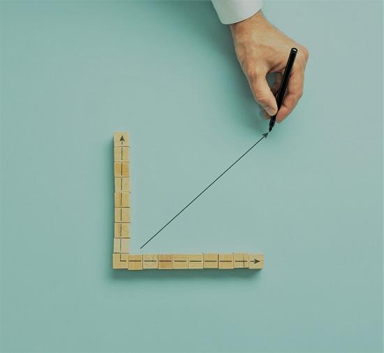 Mão de um empresário desenhando um gráfico com seta ascendente em uma imagem conceitual da economia e das finanças. Sobre fundo verde claro.